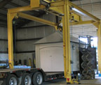 out building being loaded on semi trailer from overhead crane